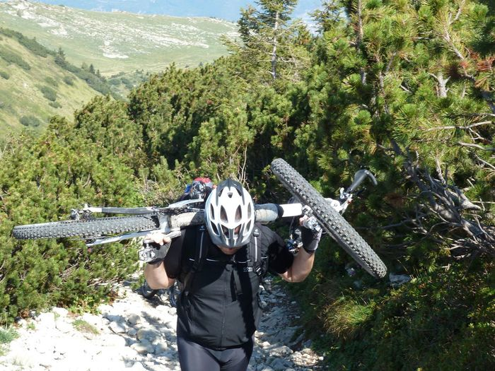 High Angle View Of Man Carrying Bicycle While Climbing On Mountain