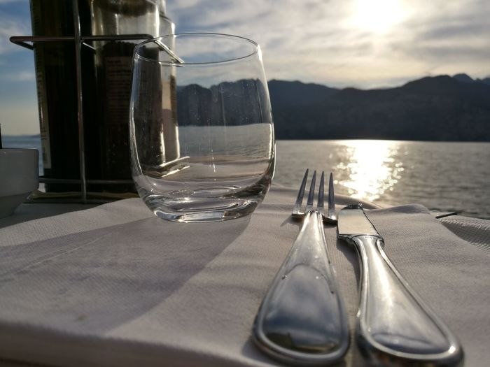 Close-Up Of Fork And Knife By Glass On Table Against River During Sunny Day