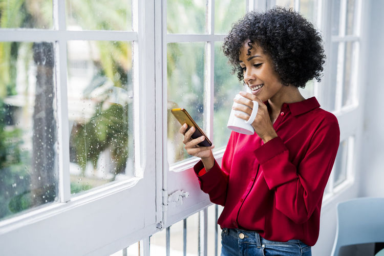 Woman holding mobile phone while standing by window