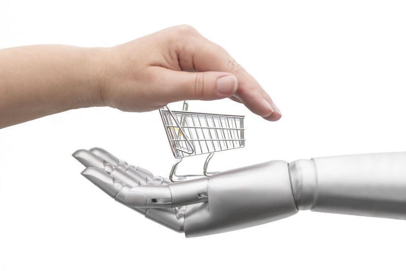 A human hand and a robot hand frame an empty shopping cart. Isolated against white background. Shopping Cart Business Economy Finance Future Hand Holding Human Hand Purchasing Robot Robot Hand Studio Shot Technology White Background
