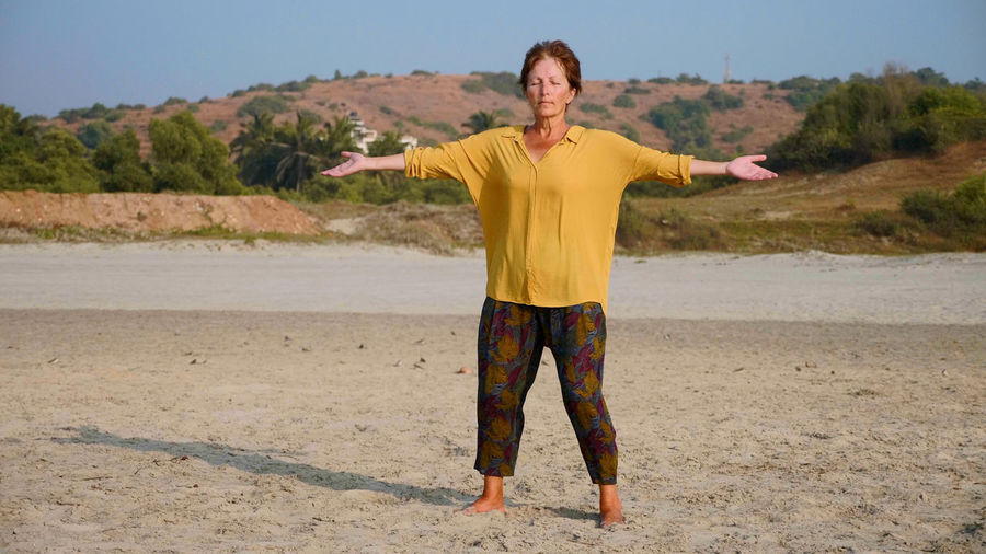 Full length of woman with arms outstretched while standing on sand at beach