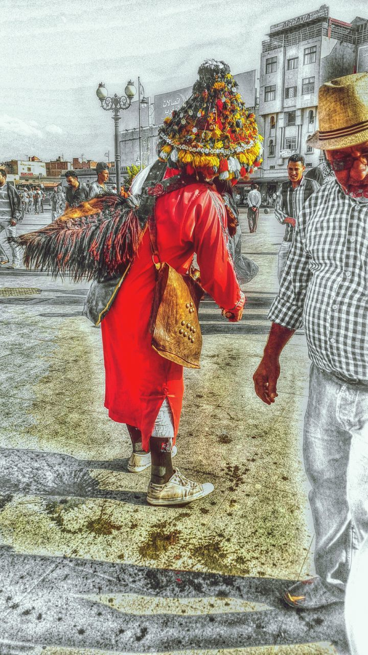 real people, traditional clothing, costume, celebration, street, built structure, walking, rear view, leisure activity, cultures, men, lifestyles, architecture, day, building exterior, two people, outdoors, carnival, red, full length, city, adult, people, adults only