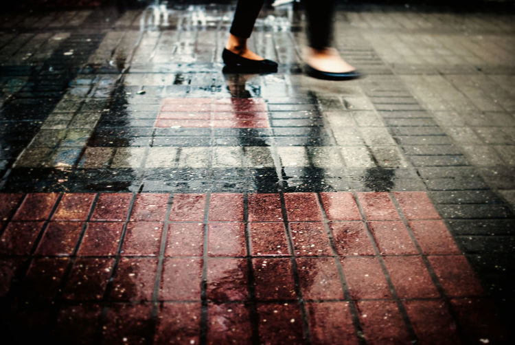 Blurred motion of woman walking on wet footpath during rainy season