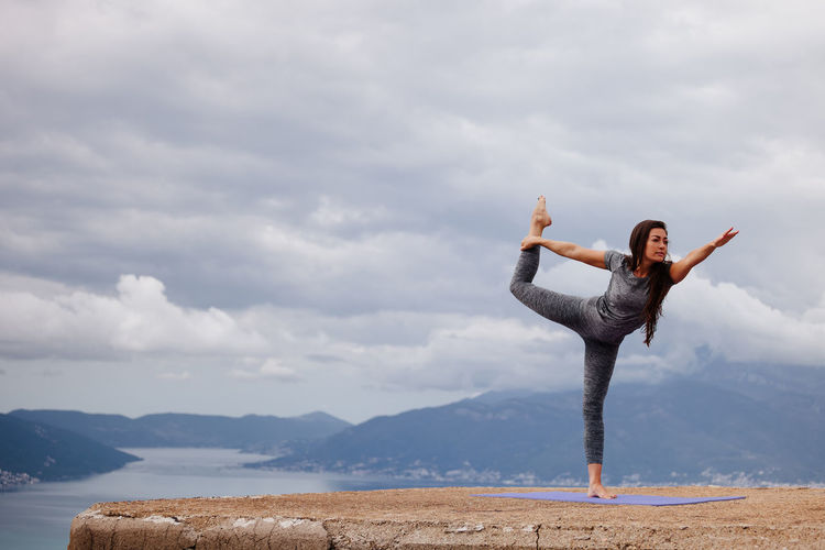 Full length of young woman exercising on cliff against sky