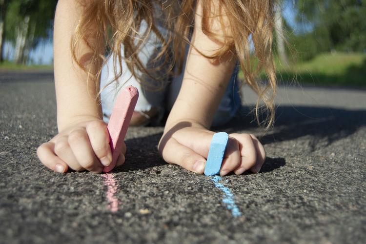 Asphalt Crayons Art Asphalt Art Body Part Casual Clothing Child Childhood Close-up Colored Crayons Day Drawing Drawing - Activity Front View Girls Hair Hairstyle Hand Human Body Part Nail One Person Outdoors Road Selective Focus Sitting Down