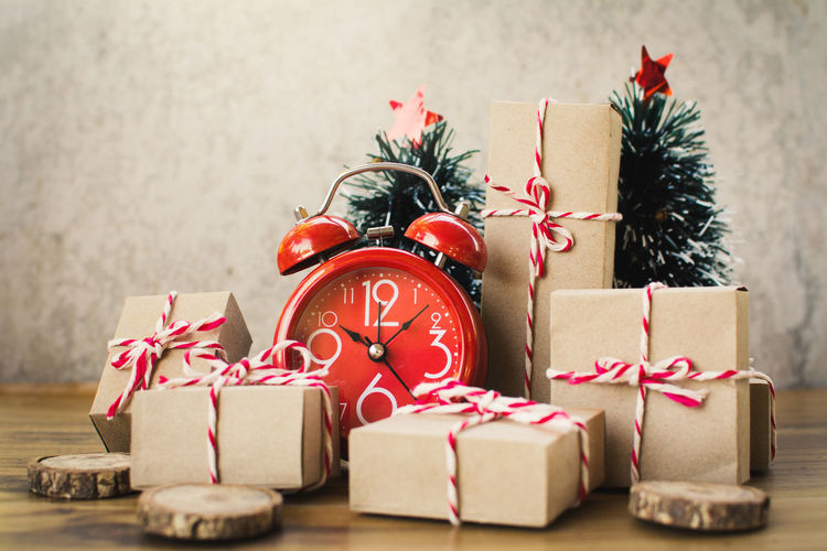 Close-up of christmas gifts and alarm clock on table