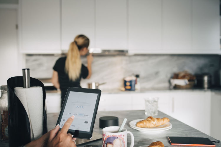 Woman using smart phone while sitting on table