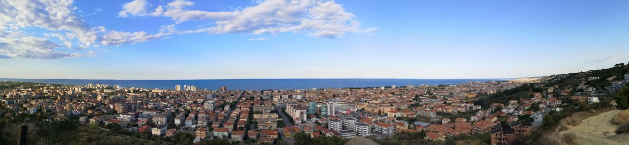 Panoramic view of town by sea against sky