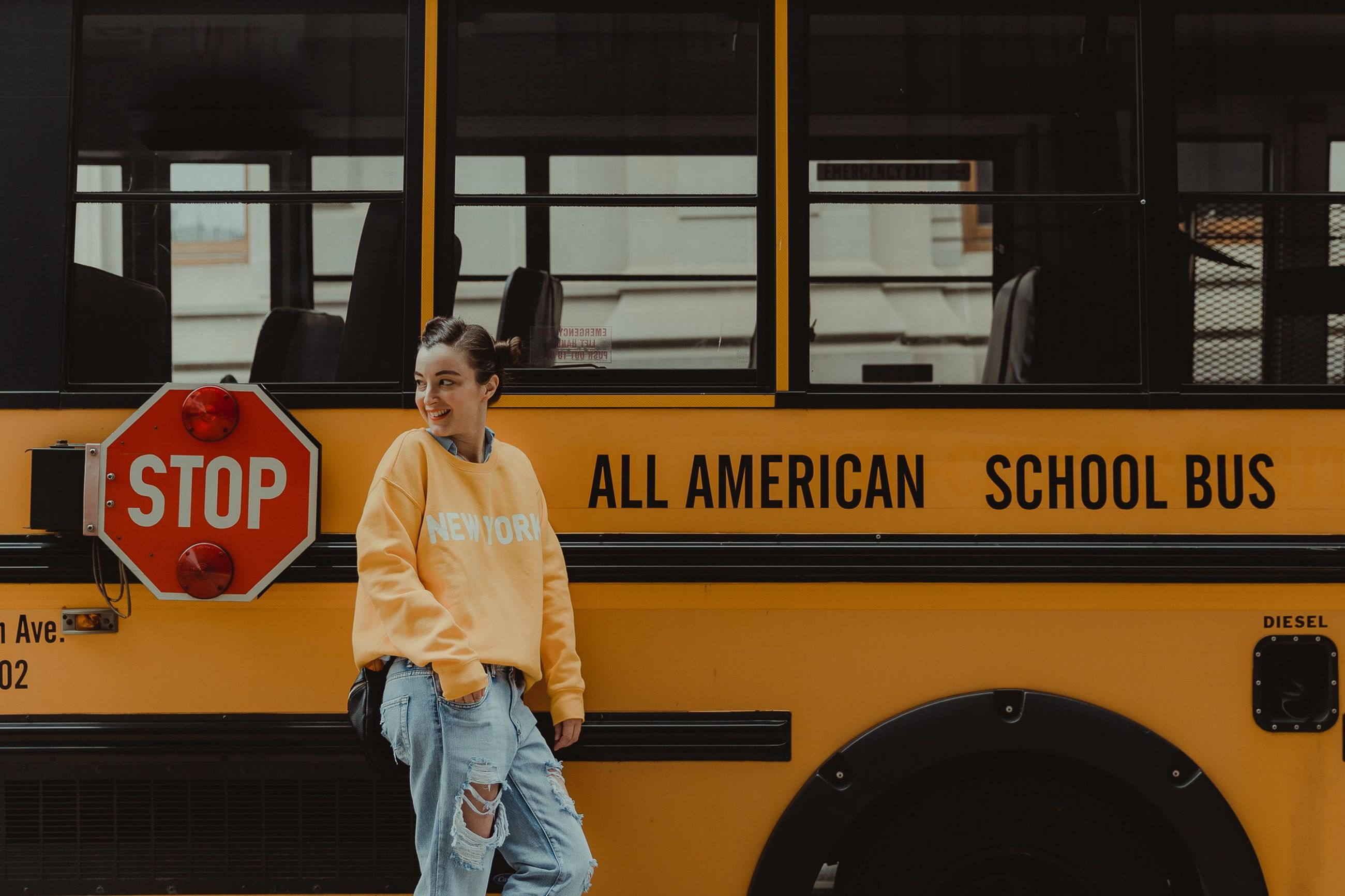 transportation, mode of transportation, real people, three quarter length, one person, yellow, public transportation, front view, bus, standing, casual clothing, lifestyles, land vehicle, leisure activity, school bus, text, communication, rail transportation