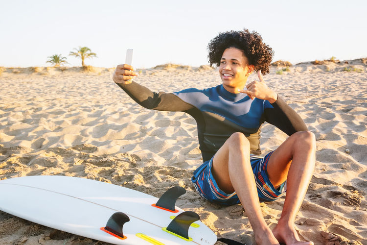 African american man sitting on the sand with surfboard takes a photo with a smartphone