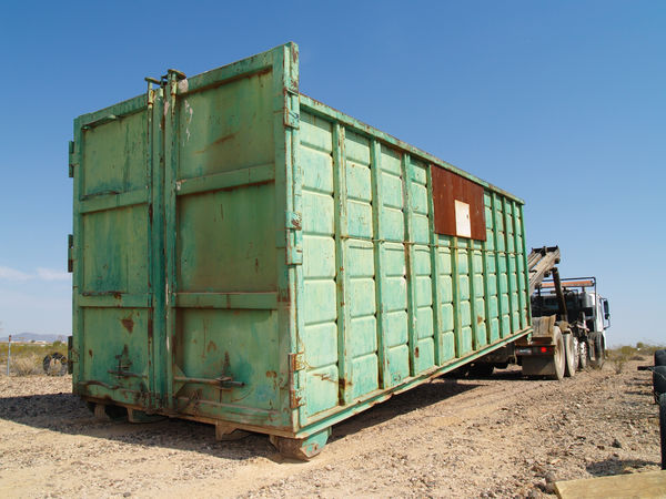 A large green metal garbage dumpster being delivered to a contruction site in Arizona. Arizona Construction Site Trash Bin Work Site Blue Cargo Container Container Day Field Industry Land Vehicle No People Outdoors Transportation Waste Disposal