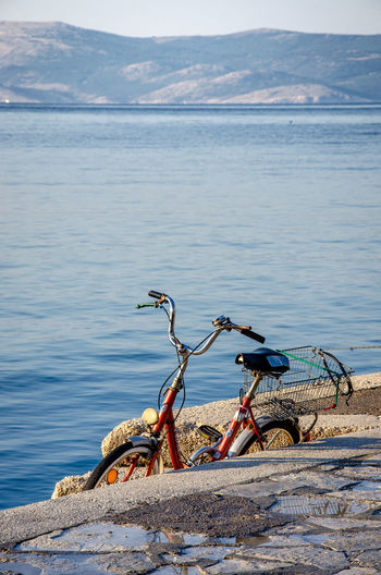 Bicycle on beach against mountain