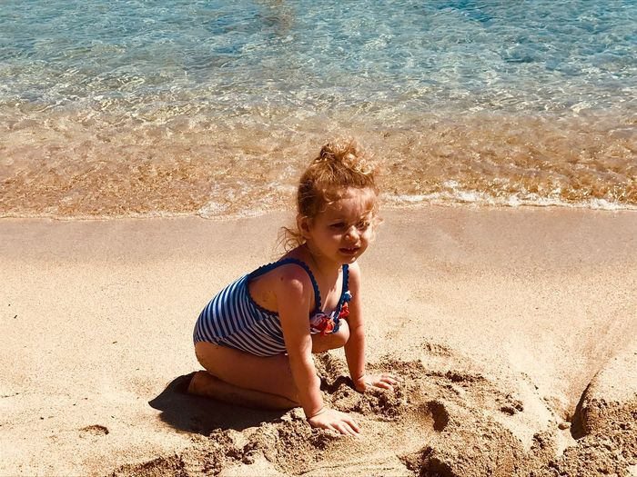 High angle view of girl playing with sand at beach