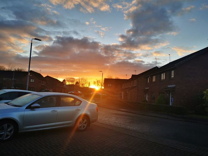 Cars on street against sky during sunset