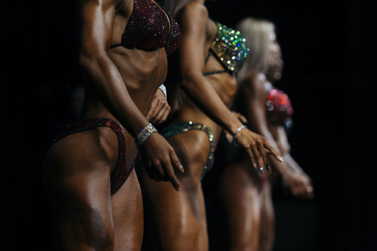 posing women in swimsuit competition fitness bikini Adult Clothing Human Body Part Women Group Of People People Togetherness Vitality Performance Arts Culture And Entertainment Young Adult Bracelet Dancing Hand Midsection Bikini Body Part Black Background Human Arm Sport Fitness Competition