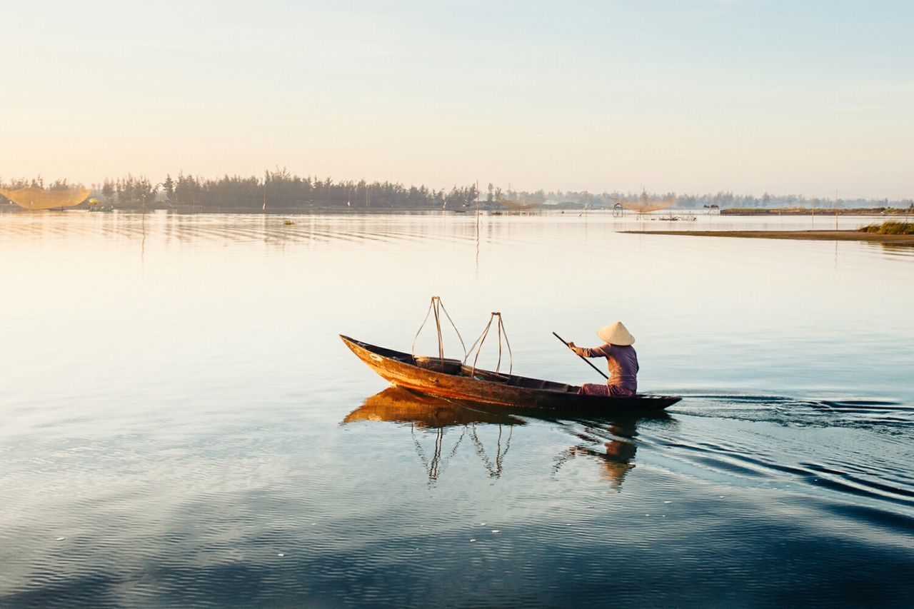 Rear view of fisherman wearing asian style conical hat on boat at lake against sky