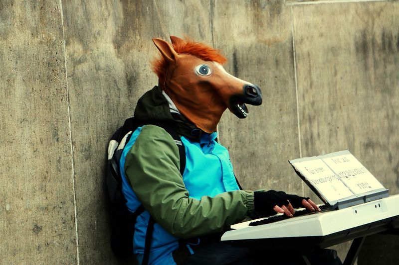 Person in horse mask playing piano sitting against wall