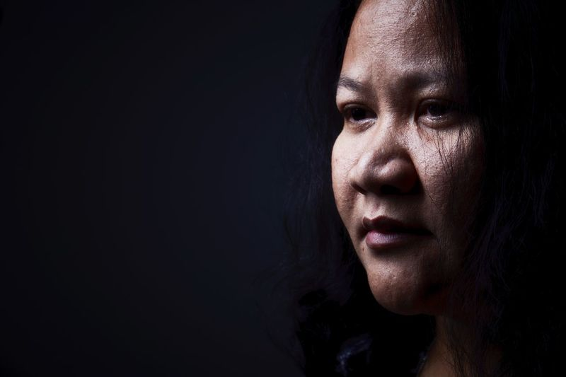 Close-Up Of Thoughtful Mid Adult Woman Looking Away Against Black Background
