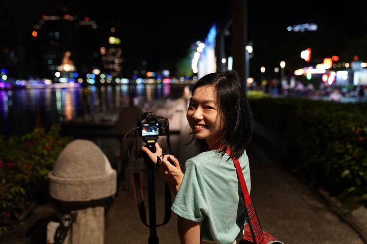Portrait of smiling woman photographing from camera in city at night