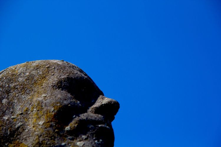 View of rocks against clear blue sky