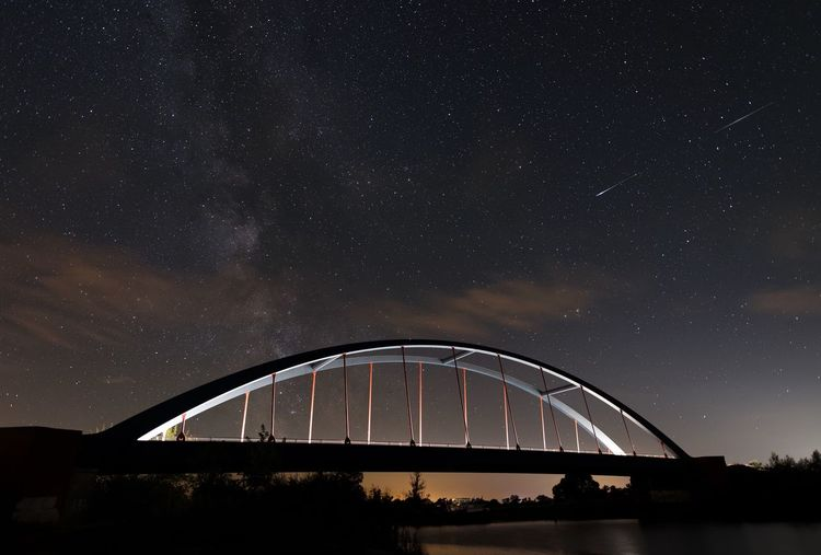 Silhouette bridge against sky at night