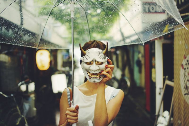Woman with umbrella covering face with mask outdoors