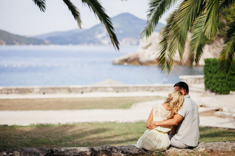 Couple sitting on palm tree by sea against sky