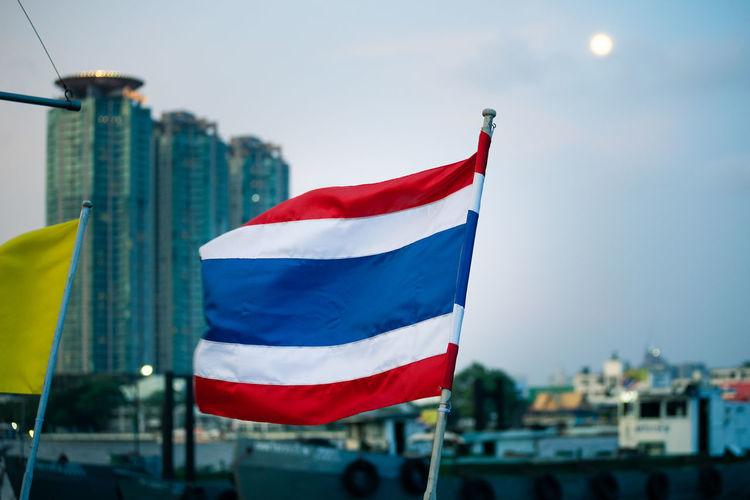 Thai flag waving in city against sky