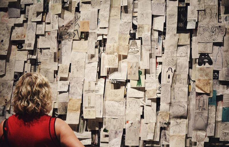 Rear View Of Woman Looking At Notes Stuck On Wall