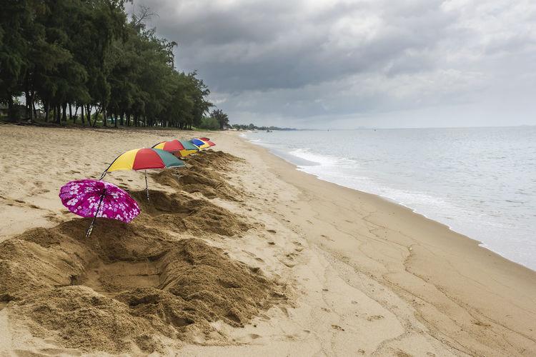 Sand spa hole and parasols ready to serve tourists at thap sakae beach prachuap khiri khan, thailand