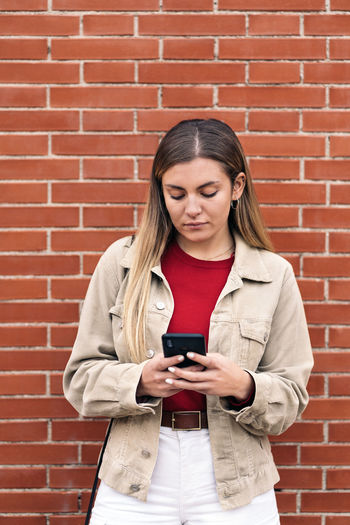 Full length of a young man using mobile phone against brick wall