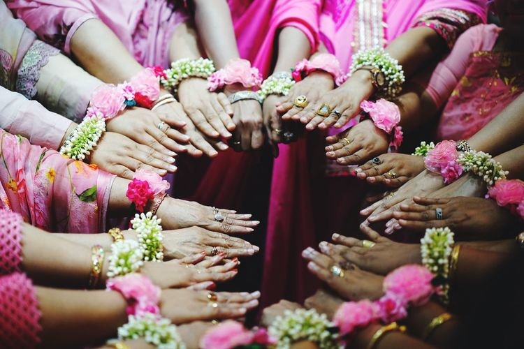 High angle view of women wearing flowers while standing in circle