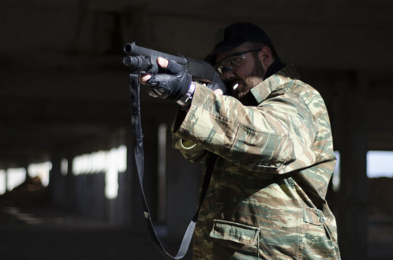 Army Soldier Shooting With Machine Gun In Basement