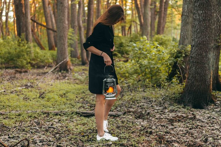 Girl staying at the forest with oil lamp. Mystic atmosphere Beautiful Woman Casual Clothing Day Forest Full Length Growth Hairstyle Land Leisure Activity Lifestyles Nature One Person Outdoors Plant Real People Standing Tree Tree Trunk Trunk Women WoodLand Young Adult Young Women