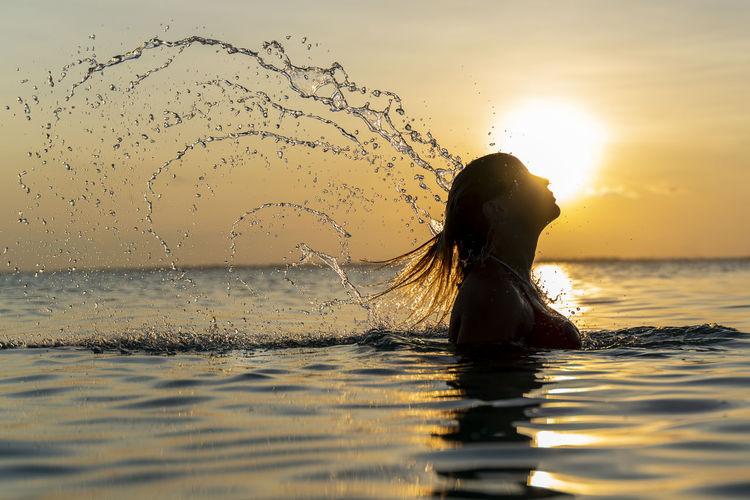 Woman splashing water against sea during sunset