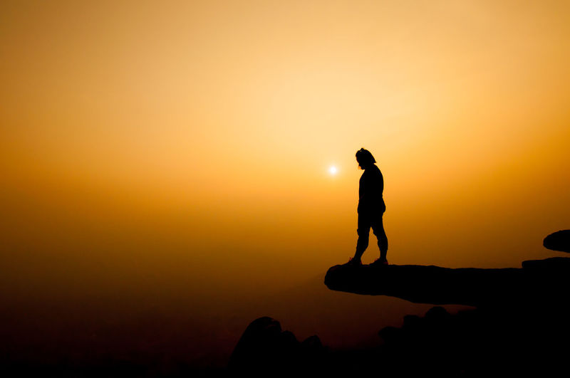 Silhouette of woman standing on cliff against sky during sunset