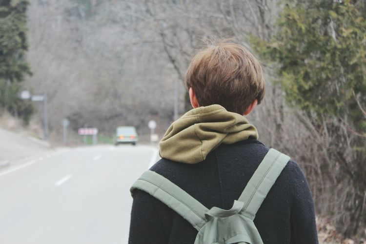 Rear view of man with backpack standing on roadside