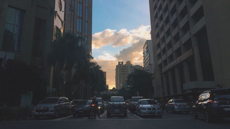 Traffic on city street by buildings against sky
