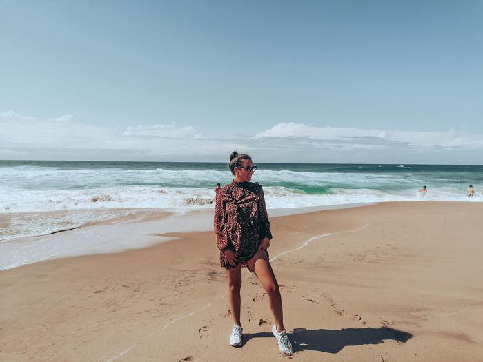 One girl standing in the beach of praia da adraga