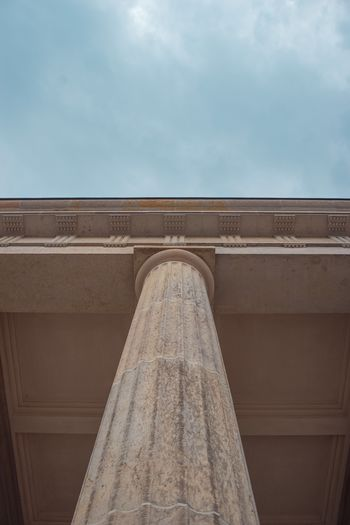 Low angle view of architectural column against cloudy sky