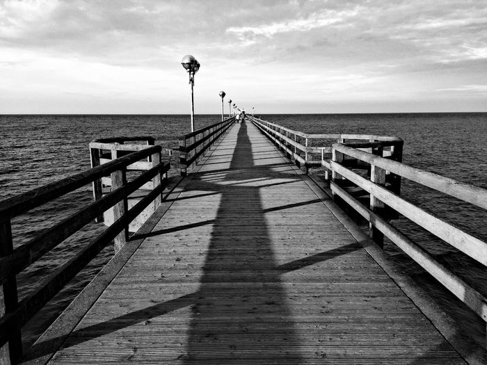 Pier on sea against cloudy sky