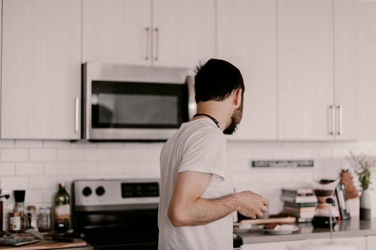 Side view of man standing in kitchen