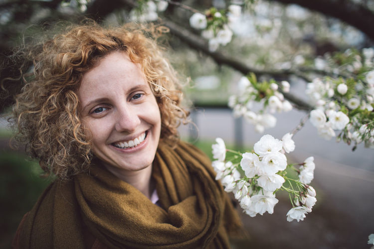 Portrait of smiling woman with curly hair by flowering tree