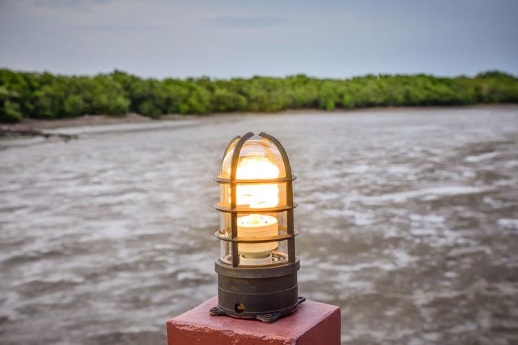 Close-Up Of Illuminated Lamp Against Sea Against Sky