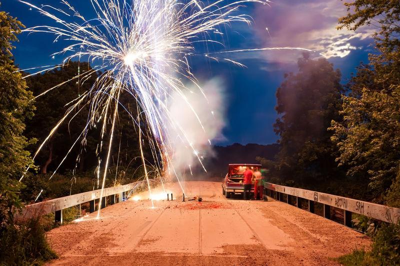 Firework display on street by car at dusk