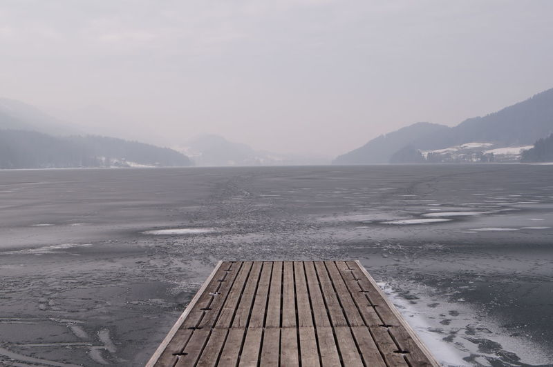 Scenic view of jetty over sea against sky during winter