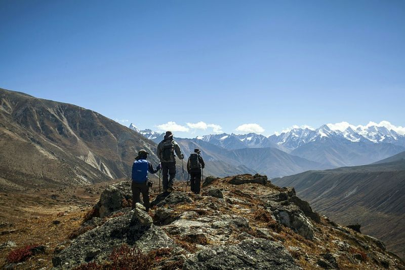 Rear view of people climbing mountain against clear blue sky
