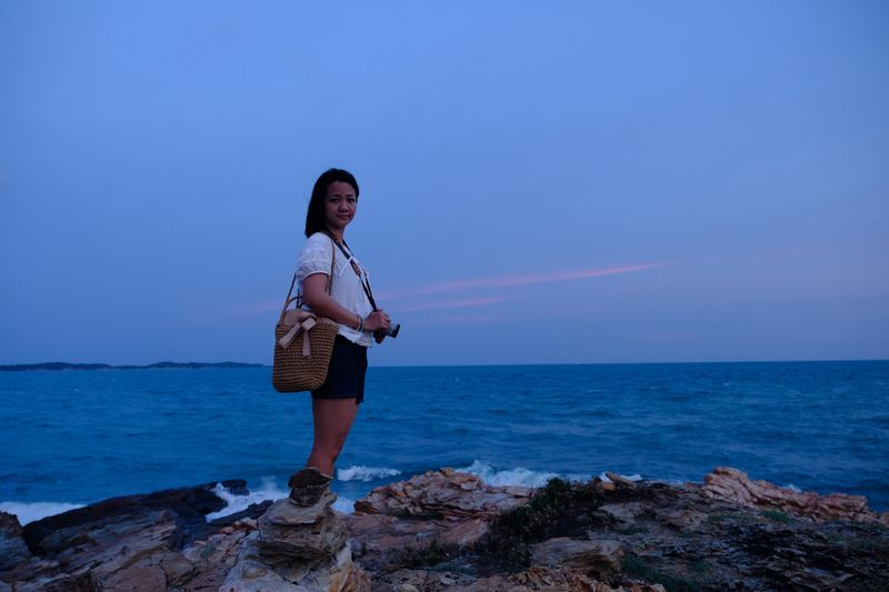 Side view of woman standing at rocky beach against sky