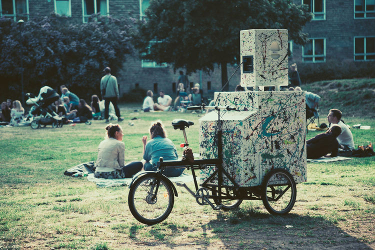 a bike with a speaker attached in a Copenhagen park, Demark. Adult Bicycle Bike Blanket Boombox Community Community Outreach Copenhagen Copenhagen, Denmark Cycle Day Estate Garden Grass Men Music Outdoors Park People Picnic Real People Speakers Urban Women Stories From The City
