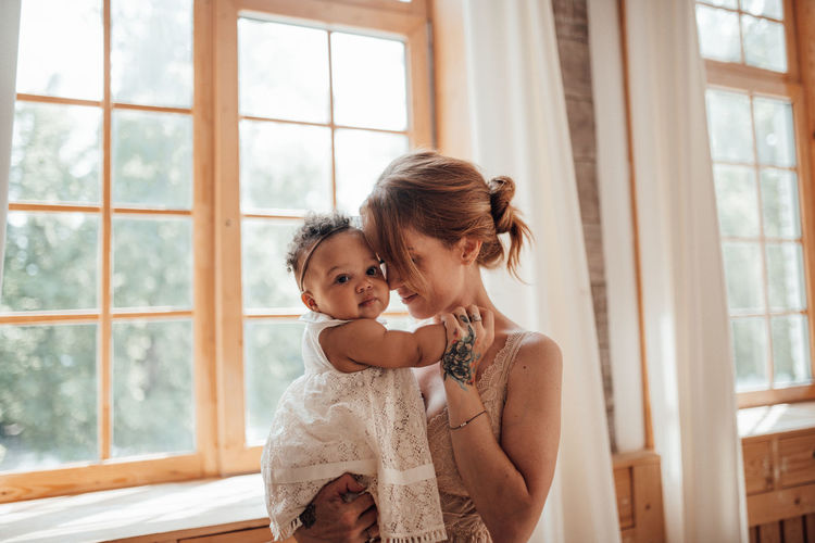 Happy mother and daughter against window